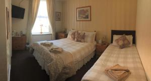 A bed or beds in a room at Warwick Court Guest House