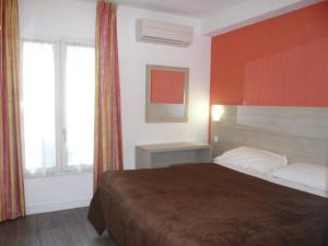 A bed or beds in a room at Hotel Parisien