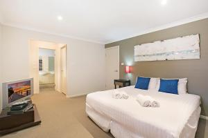 A bed or beds in a room at Peppertree Lodge Hunter Valley