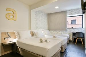 A bed or beds in a room at Hotel Laumon