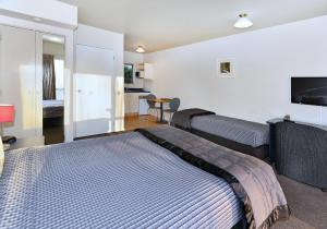 A bed or beds in a room at Arena Motel