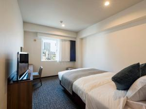 A bed or beds in a room at HOTEL MYSTAYS Sapporo Nakajima Park Annex