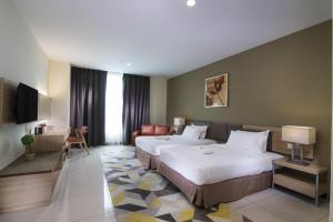 A bed or beds in a room at One Pacific Hotel and Serviced Apartments