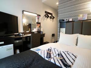 Tempat tidur dalam kamar di APA Hotel TKP Sapporo Ekimae