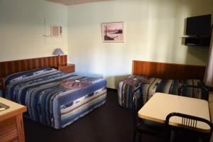 A bed or beds in a room at Alkira Motel