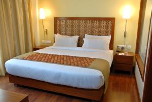 A bed or beds in a room at Cambay Grand Kukas