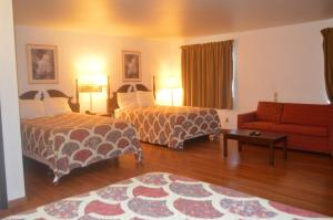 A bed or beds in a room at American Elite Inn