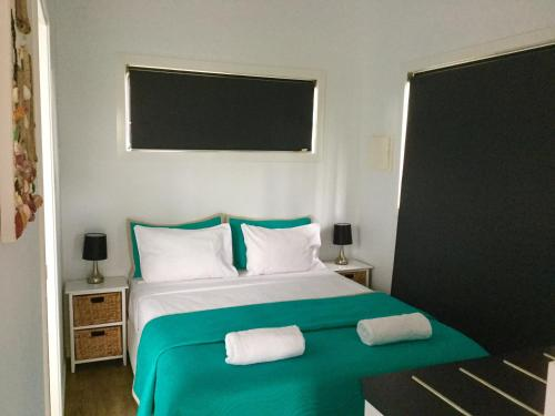 A bed or beds in a room at Club Byron Accommodation