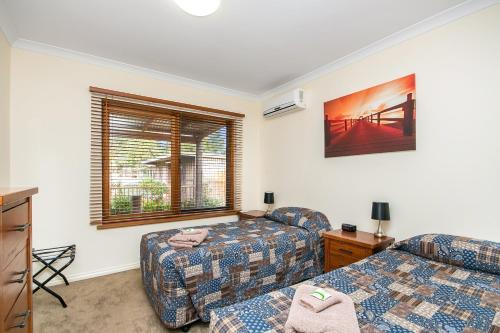 A bed or beds in a room at Coranda Lodge