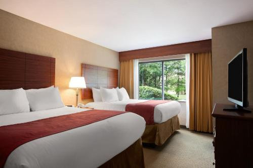 A bed or beds in a room at Ramada by Wyndham Toms River