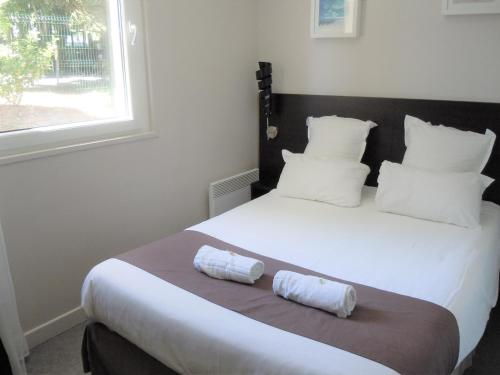 A bed or beds in a room at Sweet Home Appart'Hôtel Deauville Sud