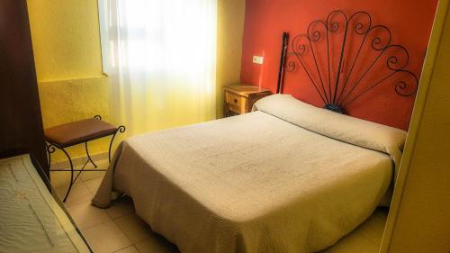A bed or beds in a room at Hostal Restaurante El Paso