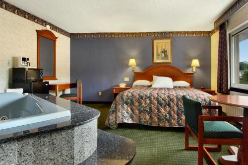 A bed or beds in a room at Days Inn by Wyndham Branford New Haven Conference Center
