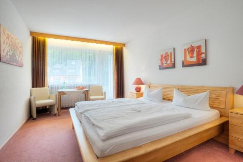 A bed or beds in a room at Hotel am Schwanenweiher