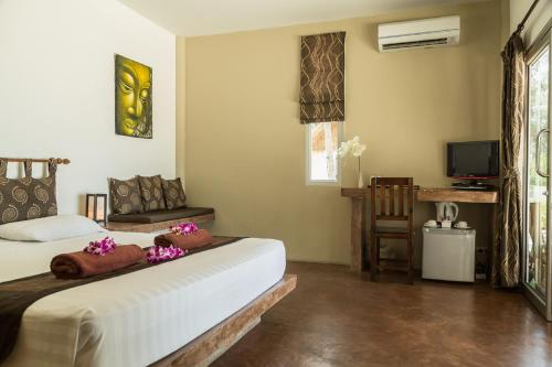 A bed or beds in a room at Angkana Hotel Bungalows