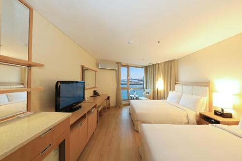 Télévision ou salle de divertissement dans l'établissement Ocean Suites Jeju Hotel