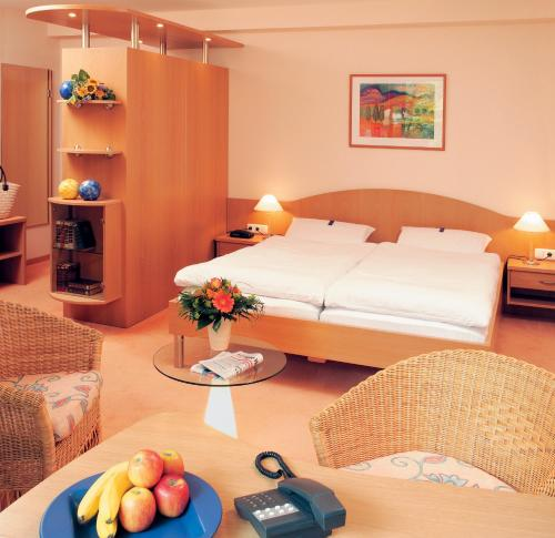 A bed or beds in a room at Moorland Hotel am Senkelteich