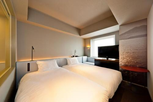 A bed or beds in a room at remm Kagoshima