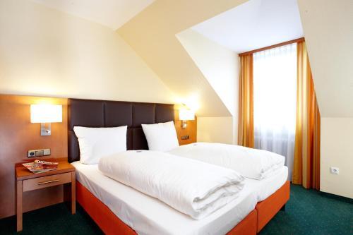 Ein Bett oder Betten in einem Zimmer der Unterkunft Hotel Grünwald