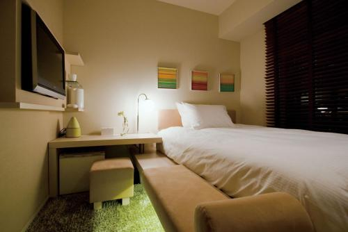 A bed or beds in a room at Hotel Resol Ikebukuro