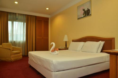 A bed or beds in a room at Grand Pacific Hotel Kuala Lumpur