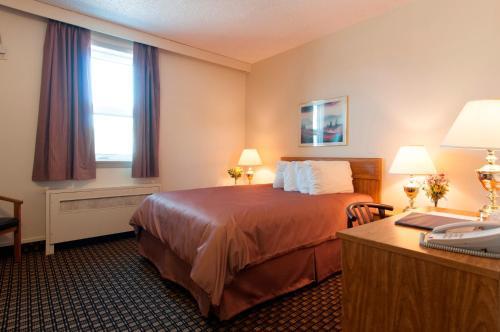 A bed or beds in a room at Assiniboine Gordon Inn on the Park