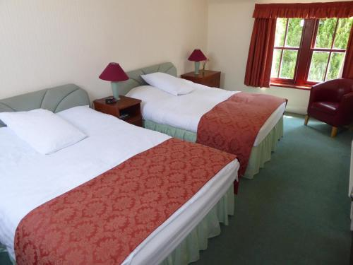A bed or beds in a room at Marykirk Hotel
