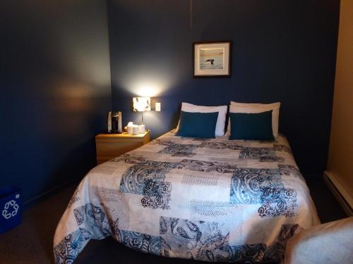 A bed or beds in a room at Motel de l'Anse a l'Eau