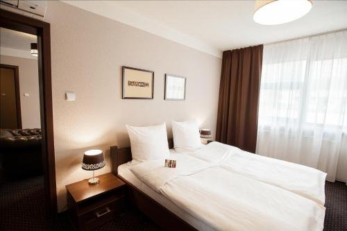 A bed or beds in a room at Hotel Diament Spodek
