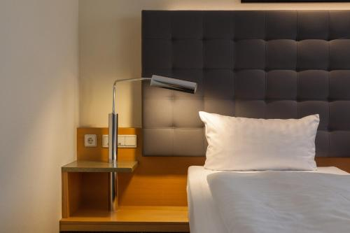 A bed or beds in a room at ABACUS Tierpark Hotel