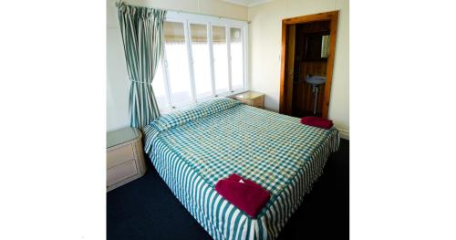 A bed or beds in a room at Brisbane Manor