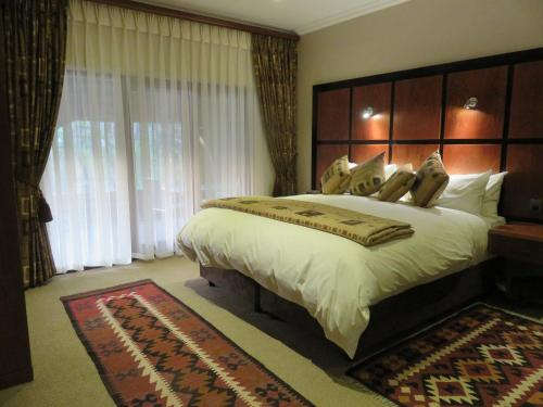A bed or beds in a room at Tladi Lodge