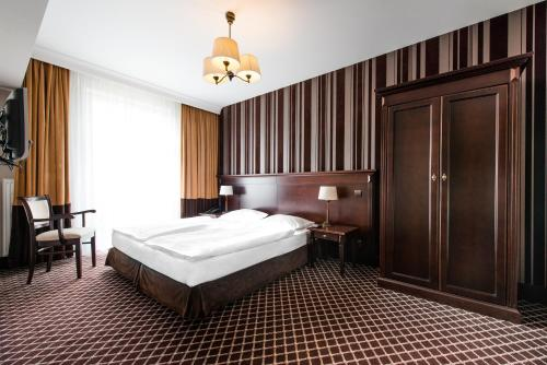A bed or beds in a room at Hotel Wileński