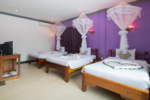 A bed or beds in a room at Tan Kang Angkor Hotel