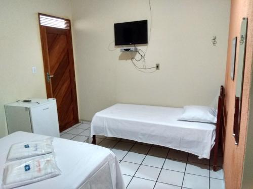 A bed or beds in a room at Pousada Terra do Sol