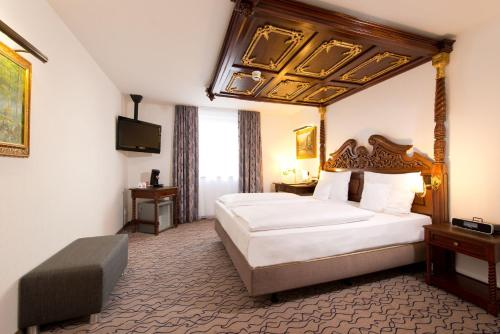 A bed or beds in a room at King's Hotel Center Superior