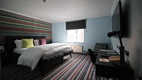 A bed or beds in a room at Village Hotel Cardiff