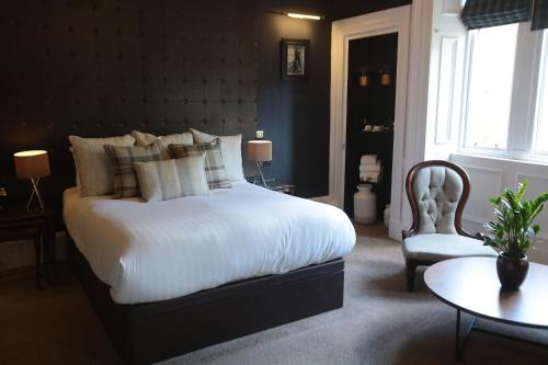A bed or beds in a room at The Belhaven Hotel