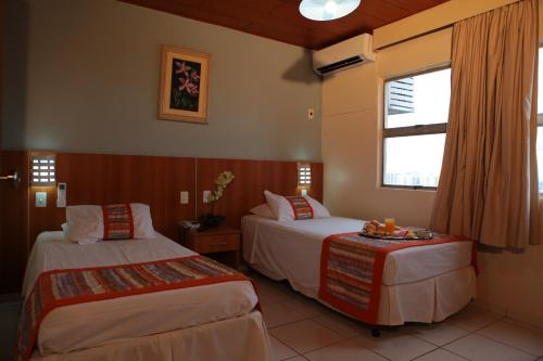 A bed or beds in a room at Mato Grosso Palace Hotel