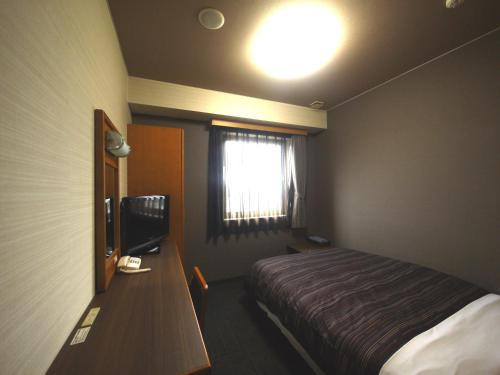 A bed or beds in a room at Hotel Route-Inn Nakatsugawa Inter