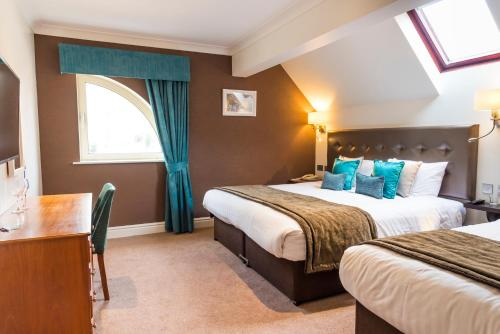 A bed or beds in a room at Ufford Park Hotel, Golf & Spa