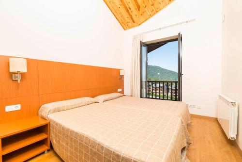 A bed or beds in a room at Guitart La Molina Aparthotel & Spa