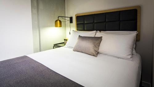 A bed or beds in a room at Haka Hotel Suites - Auckland City