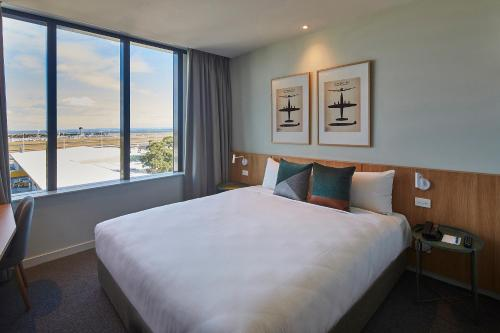A bed or beds in a room at Mantra Hotel at Sydney Airport
