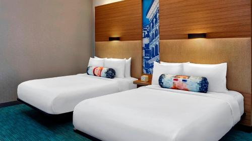 A bed or beds in a room at Aloft New York LaGuardia Airport