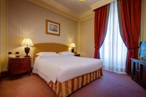 A bed or beds in a room at Excelsior Palace Palermo