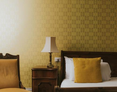 A bed or beds in a room at Healing Manor Hotel