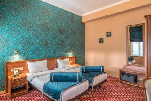 Кровать или кровати в номере Golden Tulip Borjomi