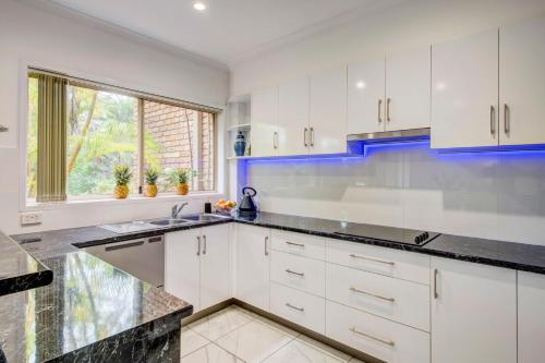 A kitchen or kitchenette at Palm Haven - Beachy Byron Townhouse
