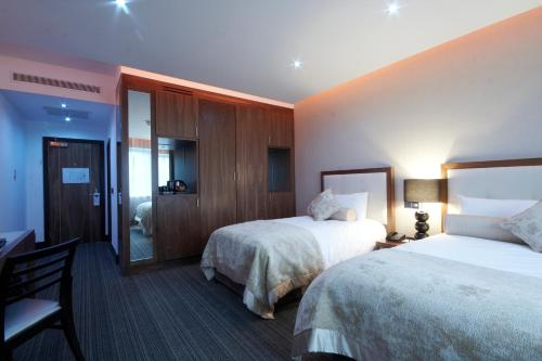 A bed or beds in a room at Rochestown Park Hotel